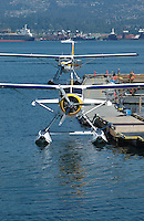 Two seaplanes tied up at dock in Coal Harbor Vancouver