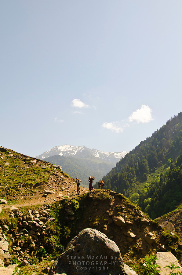 Man and woman walking on trail above the Kanka River, near Naranag, Kashmir, India.