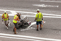 Employees from the NY Department of Transportation install new thermoplastic lane markings over the worn out older ones on the pavement in the New York neighborhood of Chelsea on Saturday, July 19, 2014.  (© Richard B. Levine)