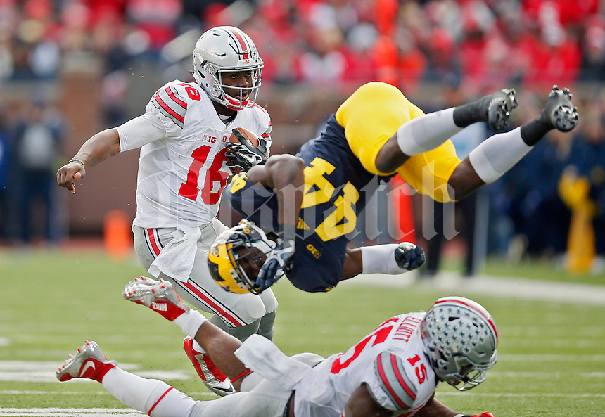 Ohio State Buckeyes running back Ezekiel Elliott (15) blocks Michigan Wolverines safety Delano Hill (44) to open a hole for Ohio State Buckeyes quarterback J.T. Barrett (16) to run through in the 3rd quarter of their game at Michigan Stadium in Arbor, Michigan on November 28, 2015.  (Dispatch photo by Kyle Robertson)