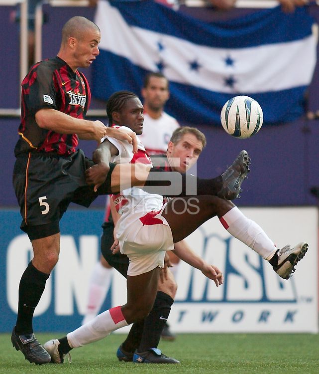Steve Jolley and Richie Williams of the MetroStars double team Damani Ralph of the Fire. The Chicago Fire defeated the NY/NJ MetroStars 2-1 on 8/24/03 at Giant's Stadium, NJ..
