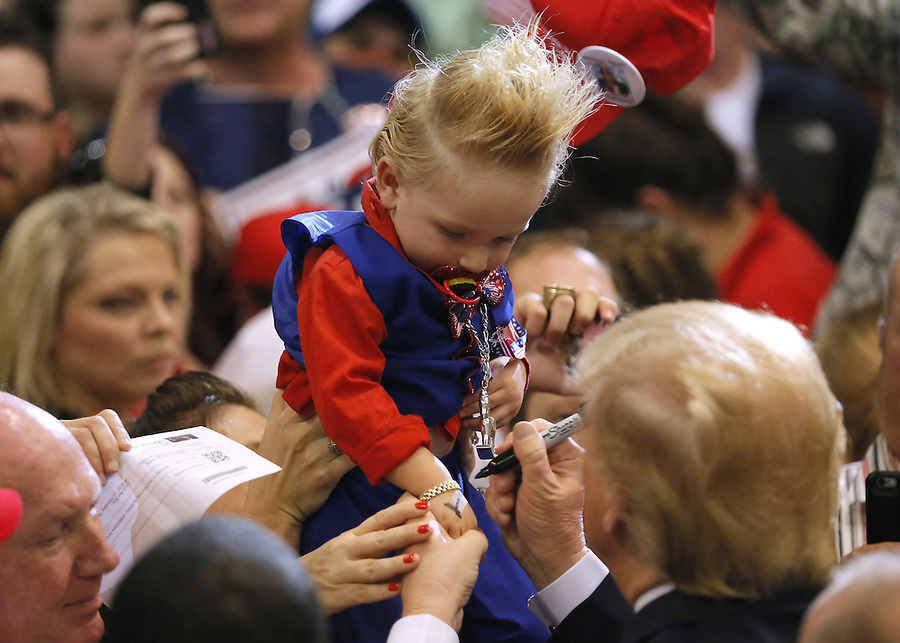 Republican U.S. presidential candidate Donald Trump signs the arm of 19-month-old Curtis Ray Jeffery II after a rally in Baton Rouge, Louisiana February 11, 2016. REUTERS/Jonathan Bachman