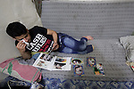 Nour, a 18-year-old Syrian man, looks at his pictures at his house in a rebel-controlled area of Aleppo, on August 13, 2015. Nour lost his leg following a bomb barrel attack by forces of Syria's President Bashar al-Assad near his house in Bustan al-Qasr district. A report from the Syrian Observatory for Human Rights (SOHR) claims that over 1,000 children have been killed in airstrikes during the nation's ongoing civil war, an additional 1.5 million people have been wounded for life in the airstrikes that have been carried out by Syria's government since the Syrian conflict. Photo by Ameer al-Halbi