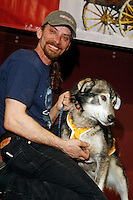 "2007 Iditarod champion Lance Mackey poses with his lead dog ""Larry"" who won the golden harness award  at the Nome awards banquet."