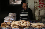 A Palestinian man bakes bread in a traditional mud oven in the West Bank city of Nablus, on February 17, 2019. Photo by Shadi Jarar'ah