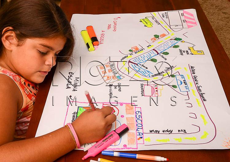 Foto de criança desenhando mapa mental, do caminho de casa até a escola, São Paulo - SP, 03/2014.