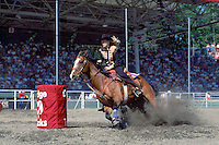 Cowgirl riding Horse in the Ladies Barrel Racing Event at the Cloverdale Rodeo, Surrey, British Columbia, Canada