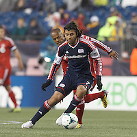 New England Revolution midfielder Juan Carlos Toja (7) dribbles as Toronto FC defender Robert Earnshaw (10) pressures. In a Major League Soccer (MLS) match, the New England Revolution (blue) defeated Toronto FC (red), 2-0, at Gillette Stadium on May 25, 2013.