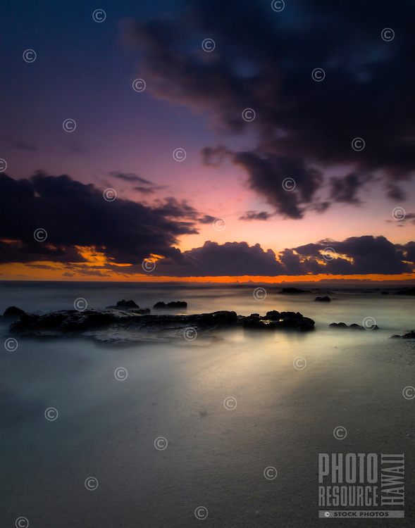 A camera's slow shutter speed flattens out the ocean's waves to create a calming sunset view of Kohanaiki Beach Park (a.k.a. Pine Trees Beach), Big Island.