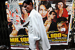 A man walks past a poster advertising a film about prostitution in Kolkata, India