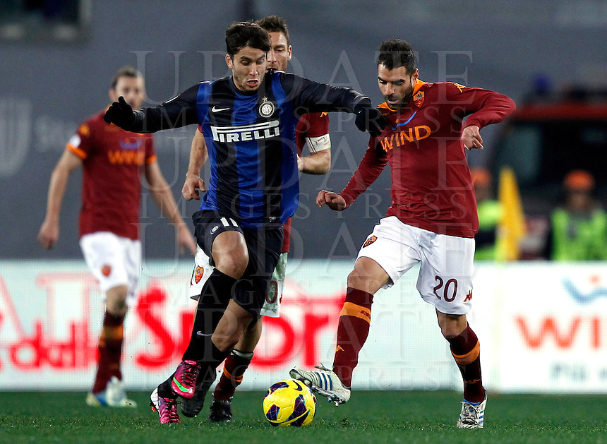 Calcio, semifinale di andata di Coppa Italia: Roma vs Inter. Roma, stadio Olimpico, 23 gennaio 2013..FC Inter midfielder Gabriel Ricardo Alvarez, of Argentina, left, is challenged by AS Roma forward Francesco Totti, center, partially hidden, and midfielder Simone Perrotta during the Italy Cup football semifinal first half match between AS Roma and FC Inter at Rome's Olympic stadium, 23 January 2013..UPDATE IMAGES PRESS/Isabella Bonotto