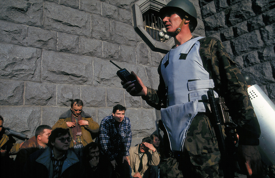 Moscow, Russia, 04/10/1993..A pro-Government militiaman watches tanks bombard the Russian Parliament while standing over captured rebels who had surrendered from the parliament building. When President Boris Yeltsin dissolved the opposition-dominated Russian Parliament,  deputies and supporters, led by Vice President Alexander Rutskoi, barricaded themselves inside the White House. After a 10 day stand-off the situation exploded into violence between pro and anti Yeltsin forces.