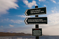 Signs at the Glen Brittle beach, Isle of Skye, Scotland. The signs, containing both the Gaelic and english names of locations, point to Rubh an Dunain and Loch Coruisk. These are walking trails and not passable in other way - thus the Take Care warning below. The visible water is Loch Brittle.