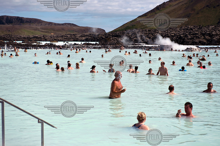 Visitors to the Blue Lagoon, a health spa utilising water from a nearby geothermal power plant.