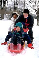 Multicultural teens age 10 - 15 sledding.   St Paul Minnesota USA