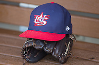 A US Collegiate National Team hat sits on top of a glove in the dugout prior to the game against the Cuban National Team at BB&T BallPark on July 4, 2015 in Charlotte, North Carolina.  The United State Collegiate National Team defeated the Cuban National Team 11-1.  (Brian Westerholt/Four Seam Images)