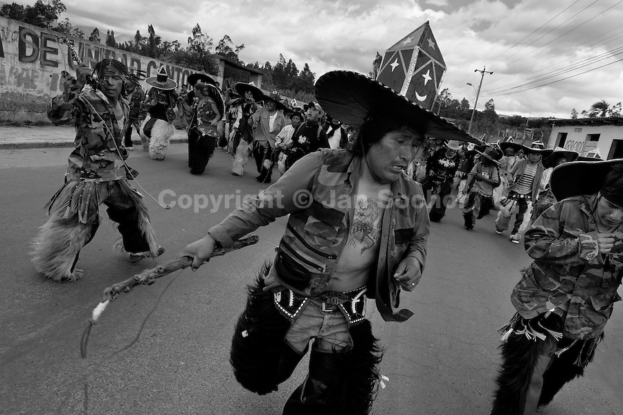 Indians, wearing military camouflage, dance furiously during the Inti Raymi (San Juan) festivities in Cotacachi, Ecuador, 24 June 2010. 'La toma de la Plaza' (Taking of the square) is an ancient ritual kept by Andean indigenous communities. From the early morning of the feast day, various groups of San Juan dancers from remote mountain villages dance in a slow trot towards the main square of Cotacachi. Reaching the plaza, Indians start to dance around. They pound in synchronized dance rhythm, shout loudly, whistle and wave whips, showing the strength and aggression. Dancers from either the upper communities (El Topo) or the lower communities (La Calera), joined in respective coalitions, seek to conquer and dominate the square and do not let their rivals enter. If not moderated by the police in time, the high tension between groups always ends up in violent clashes.