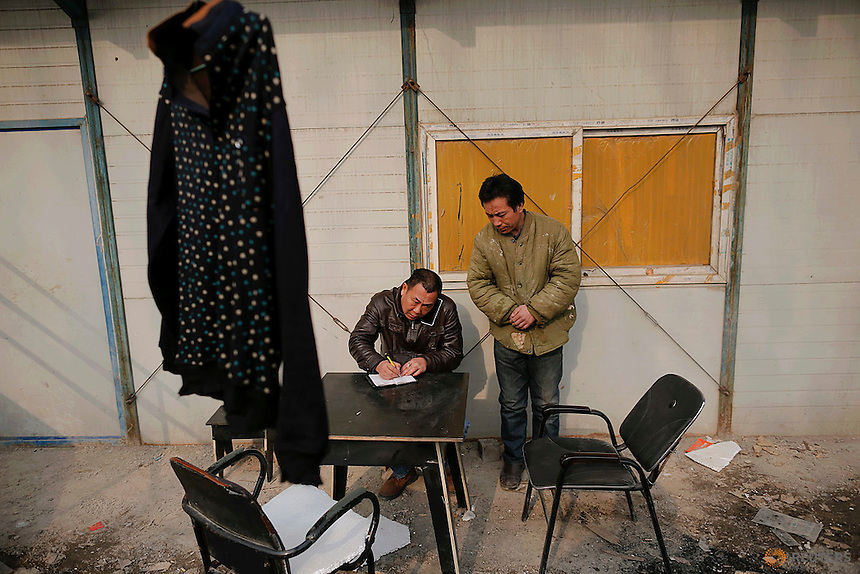 A migrant worker takes notes as he talks on phone at the construction site of Changxiang Gardens development complex in Fengrun District, Tangshan City, Hebei province, China January 28, 2016. REUTERS/Damir Sagolj