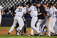 Tampa Yankees second baseman Nick Solak (39) is mobbed by teammates, including Austin Aune (31) and Trey Amburgey (17), after a walk off base hit during a game against the Fort Myers Miracle on April 12, 2017 at George M. Steinbrenner Field in Tampa, Florida.  Tampa defeated Fort Myers 3-2.  (Mike Janes/Four Seam Images)