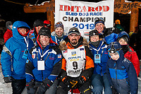 Pete Kaiser poses with Principal sponsor ExxonMobil at the Nome finish line after winning the 2019 Iditarod Trail Sled Dog Race. Pete's winning time is 9 days 12 hours 39 minutes and 6 seconds<br /> <br /> Photo by Jeff Schultz/  (C) 2019  ALL RIGHTS RESERVED