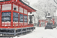 During a winter snowfall, the Fukashi Shrine looks like a traditional Japanese woodblock print. Matsumoto, Nagano, Japan.