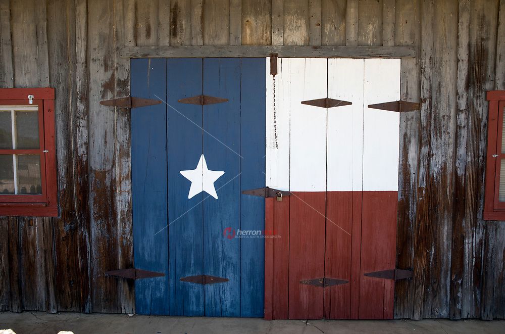 View of a Texas LoneStar Flag painted on a barn door at a farm in the Texas Hill Country.
