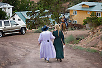 """Aug 9, 2008 -- COLORADO CITY, AZ: Members of the Jessop family walk back down to their home after a picnic at the Jessop home in Colorado City, AZ. The Jessops are polygamist members of the FLDS. Colorado City and neighboring town of Hildale, UT, are home to the Fundamentalist Church of Jesus Christ of Latter Day Saints (FLDS) which split from the mainstream Church of Jesus Christ of Latter Day Saints (Mormons) after the Mormons banned plural marriage (polygamy) in 1890 so that Utah could gain statehood into the United States. The FLDS Prophet (leader), Warren Jeffs, has been convicted in Utah of """"rape as an accomplice"""" for arranging the marriage of teenage girl to her cousin and is currently on trial for similar, those less serious, charges in Arizona. After Texas child protection authorities raided the Yearning for Zion Ranch, (the FLDS compound in Eldorado, TX) many members of the FLDS community in Colorado City/Hildale fear either Arizona or Utah authorities could raid their homes in the same way. Older members of the community still remember the Short Creek Raid of 1953 when Arizona authorities using National Guard troops, raided the community, arresting the men and placing women and children in """"protective"""" custody. After two years in foster care, the women and children returned to their homes. After the raid, the FLDS Church eliminated any connection to the """"Short Creek raid"""" by renaming their town Colorado City in Arizona and Hildale in Utah. A member of the Jessop family weeds the community corn plot in Colorado City, AZ. The Jessops are a polygamous family and members of the FLDS. Photo by Jack Kurtz / ZUMA Press"""