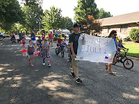 NWA Democrat-Gazette/SPENCER TIREY Brandon and Jennifer Stephens carry a 4th of July sign Wednesday, July 4, 2018 ahead of the parade of kids in their Turtle Creek Place subdivision in Rogers. The parade was organized by Camryn Hodge an 8-year-old who wanted to show how much she loved America and wanted to make new friends in the neighborhood.