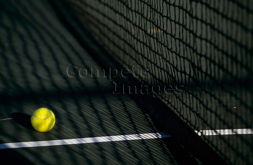 Tennis ball next to net on a grass court