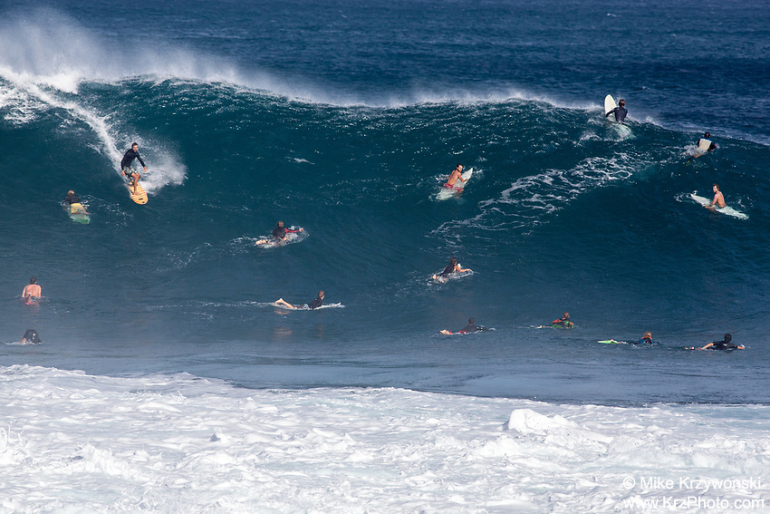 Surfer navigating through a crowded lineup on a big wave at Pipeline, North Shore, Oahu