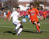 Alex Martinez (15) of North Carolina State prepares to chip the ball over Cameron Owens (29) of Virginia Tech during the game at Ludwig Field in College Park, MD. Virginia Tech defeated North Carolina State, 3-2, in the ACC tournament play-in game.