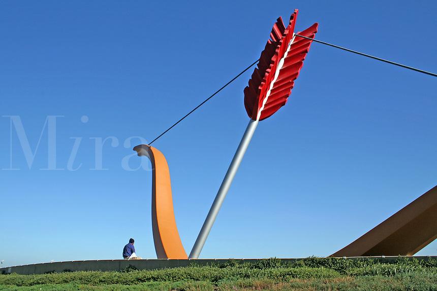 Man sitting at base Cupid?s Span sculpture Embarcadero, San Francisco California