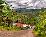 The switchback near the top of this road provided me a fabulous view of the countryside surrounding Sampaloc.  This nearly vertical road down to one of the poorer neighborhoods on the outskirts of Sampaloc is nearly impassible in rain.  The town of Sampaloc itself is seen as rooftops in the middle distance beyond.  (HDR Image)
