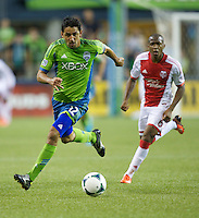 Leonardo Gonzalez, left, of the Seattle Sounders FC dribbles the ball in front of Darlington Nagbe of the Portland Timbers during play at CenturyLink Field in Seattle Saturday August, 3, 2013. The Sounder won the match 1-0.