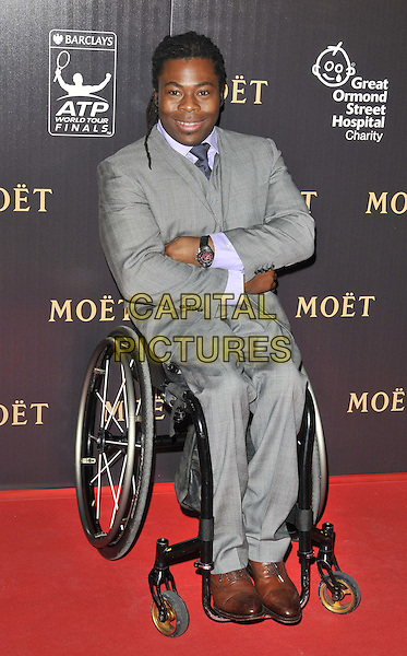 Ade Adepitan.attended the Barclays ATP World Tour Finals official launch party, Battersea Power Station, Cringle St., London, England, UK, 17th November 2011..full length in wheelchair grey gray suit .CAP/CAN.©Can Nguyen/Capital Pictures.