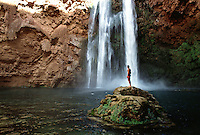 Scenic view of the refreshing Havasuapi Falls; a tourist stands on the rocks. Grand Canyon, Arizona.