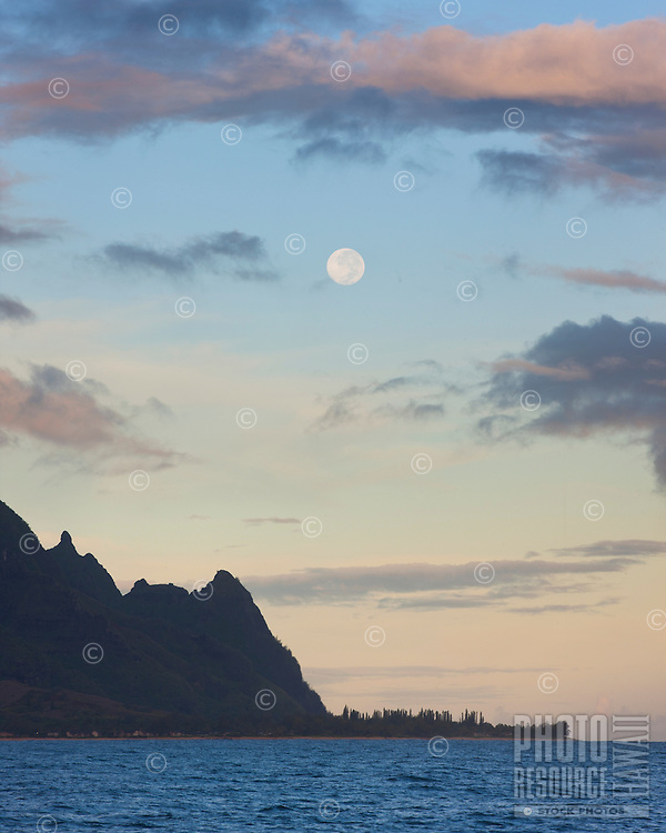 The full moon sets at sunrise over Mt. Makana (Bali Hai) on Kauai.