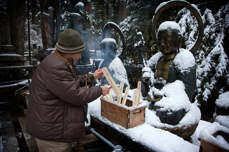 (En) January 2010 - Koyasan, Japan.  Near the Tamagawa holy river in the Oku-no-In cimetery, pilgrims bring thin pieces of wood (mizumeke toba) as an offering to bodhisattvas (Jizo, Fudo and Kannon). The piece of wood is then purified with water and fire. (Fr) Janvier 2010 - Koyasan, Japon. Pres de la riviere sacree Tamagawa dans le cimetiere de l'Oku-no-in, les pelerins offrent de fines plaques de bois (mizumeke toba) devant les statues des divinites bouddhistes (Jizo, Fudo et Kannon) avant de les purifier par le feu et l'eau.