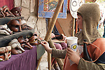A boy dressed as a knight holds a soft drink cup while looking at leather masks at the Renaissance Pleasure Faire at Santa Fe Dam Recreation Area, Los Angeles, County, CA