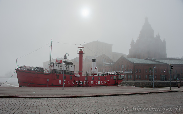 Relandersgrund lightship is docked at Helsinki harbour and is shrouded in fog.