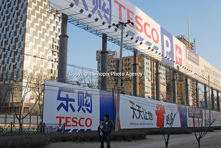 A large billboard at the Tesco supermarket that recently opened in Beijing, China. Tesco has joined with Ting Hsin, a 25-strong, upscale hypermarket based in the Shanghai region, in a deal worth £140m last year and has started re-branding and opening the stores with the familiar Tesco logo..27 Jan 2007