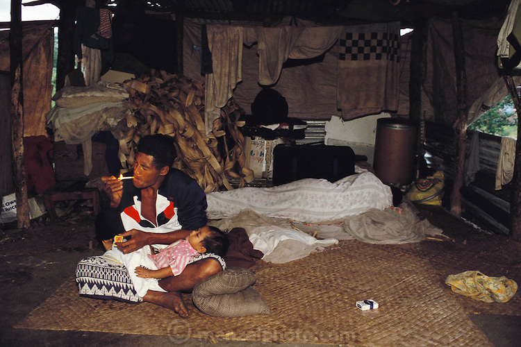 Alatupe Alatupe lights his first cigarette of the day while his 11-month-old son naps in his lap and his wife sleeps. The Lagavale family lives in a 720-square-foot tin-roofed open-air house in Poutasi Village, Western Samoa. The Lagavales have pigs, chickens, a few calves, fruit trees and a vegetable garden. Material World Project.