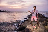 Negombo, portrait of a man fishing on the wave break at Negombo Beach, West Coast of Sri Lanka, Asia. This is a portrait of a man fishing on the wave break at Negombo Beach, West Coast of Sri Lanka, Asia.