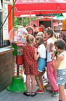 Girls age 9 through 12 buying gum balls from a machine.  Chechocinek Poland