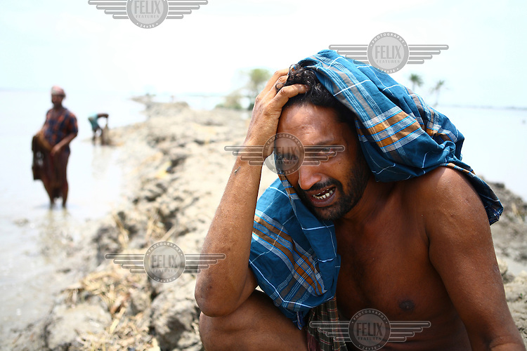A man grieves as he sits on land washed away by Cyclone Aila. Thousands of people were displaced in Shyamnagar Upazila, Satkhira district after Cyclone Aila struck Bangladesh on 25/05/2009, triggering tidal surges and floods..