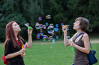 Girls blow soap bubbles during a soap bubble day in a public park in Budapest, Hungary on August 25, 2013. ATTILA VOLGYI