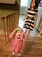 SELLERSVILLE, PA -  MARCH 7:  Emma Davies (L), 1 year old, walks through the dining room as her sister Lily (R), 6 follows March 7, 2014 in Sellersville, Pennsylvania. Emma Davies is suffering from a rare hematological disease. She will be getting a bone marrow transplant from her older sister. With bills stacking up, a friend of the Davies family has set up an online fundraiser to help.(Photo by William Thomas Cain/Cain Images)