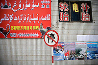 Billboards in Arabic script advertise Uighur businesses in the Uighur section of Urumqi, Xinjiang, China.