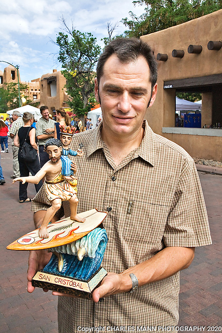 The Santa Fe Spanish Market, held in July, fills the Santa Fe Plaza with artists parton and visitors all celebrating traditional Spanish colonial arts. It is held side by side with the Contemporary Spanish Market which features modern Hispanic artists. Sculptor, painter and lothogrpaher Gustavo Victor Goler won in a new category oat Spanish Market with his image of St. Christopher on a surfboard.