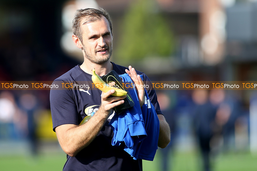 AFC Wimbledon substitute, James Hanson walks across the pitch ahead of kick-off carrying a banana during AFC Wimbledon vs Portsmouth, Sky Bet EFL League 1 Football at the Cherry Red Records Stadium on 13th October 2018